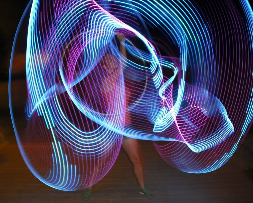 Photo of Carrie hooping at night with LED hoops!