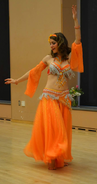 Photo of Carrie in orange belly dance costume.